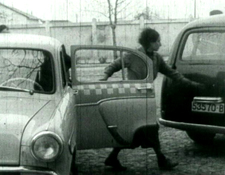 Re-enactment of the bank robbery -- Monica Sevianu moves toward the bank car -- still from the 1961 film Reconstituirea