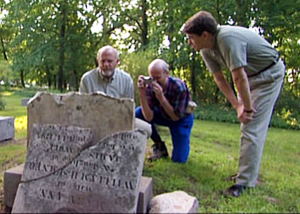 three people looking at a grave stone in the DeWolf's family cemetery in Bristol, Rhode Island