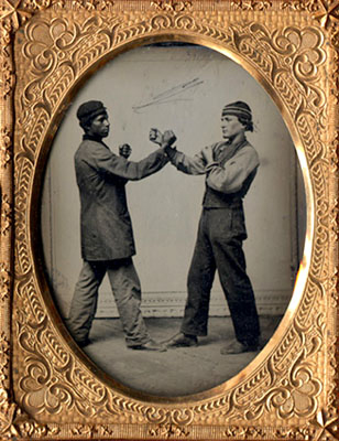 staged studio image of two men boxing circa 1860-65